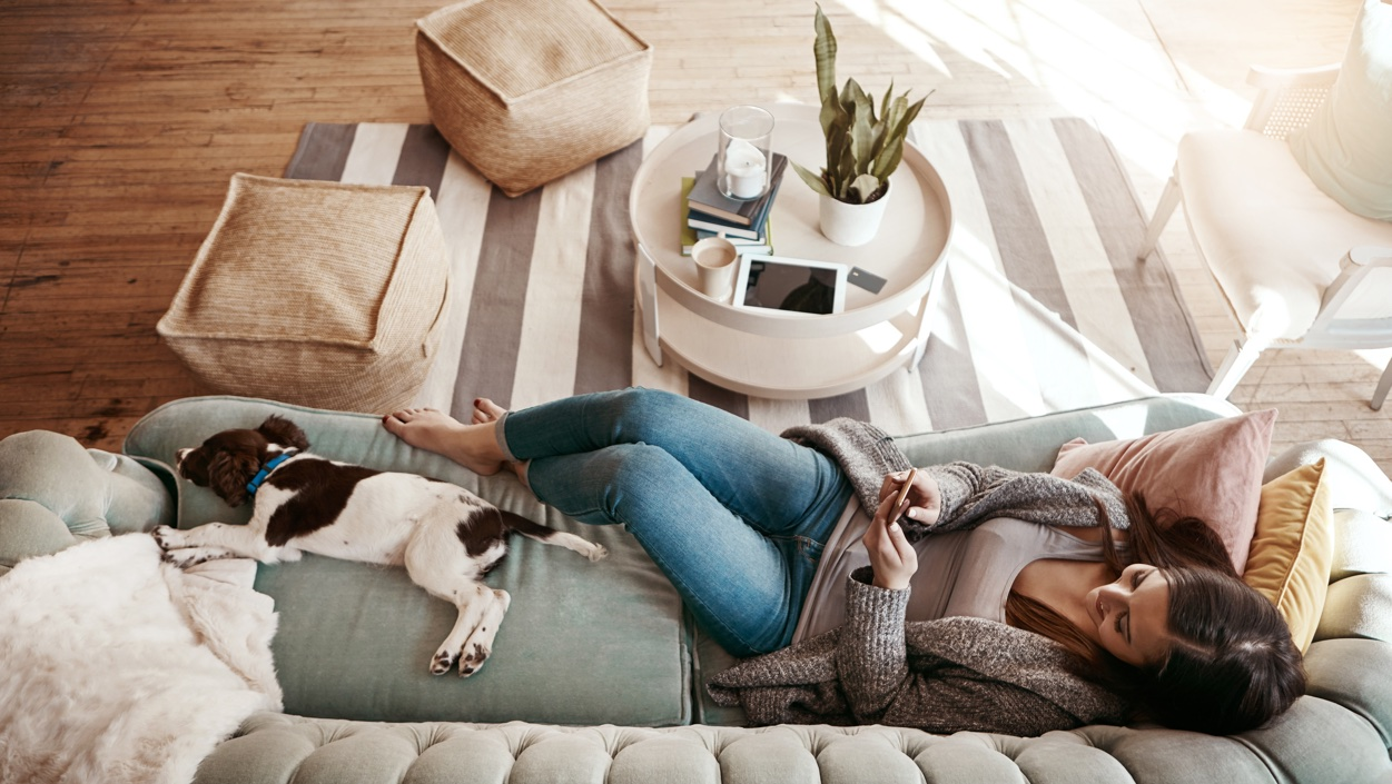 Woman lying on a couch in a living room, with a small black and white dog lying beside her