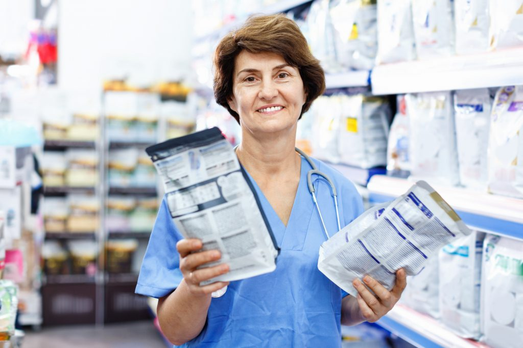 Older female veterinarian standing in an aisle of pet food inventory, she's holding a small bag of food in each hand and smiling at the camera