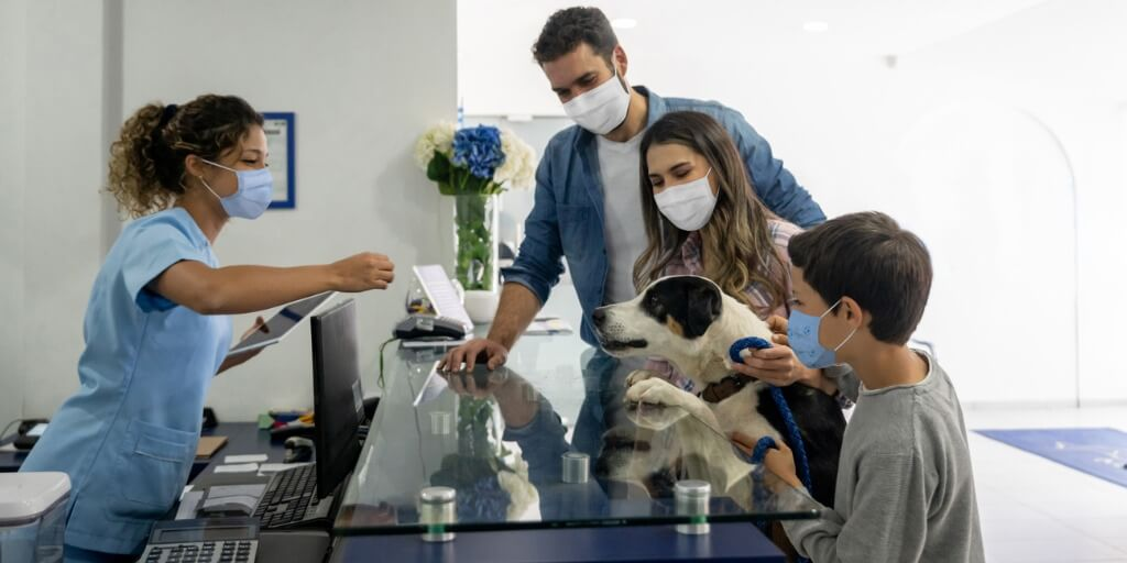 family wearing masks with their dog at the veterinarian