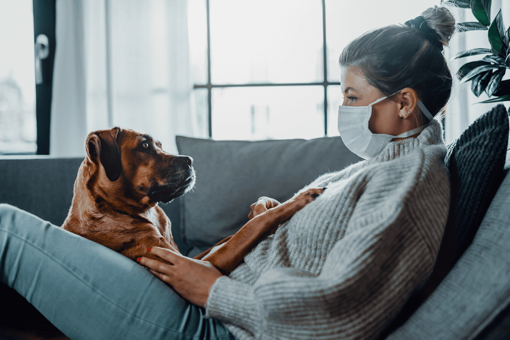 woman wearing a face mask sitting on a couch with her dog