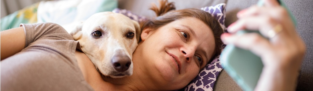 woman and dog snuggling in bed while she looks at her smartphone
